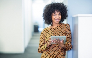 Portrait of woman using digital tablet in office